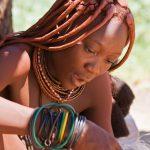 Beautiful Himba woman sewing while singing